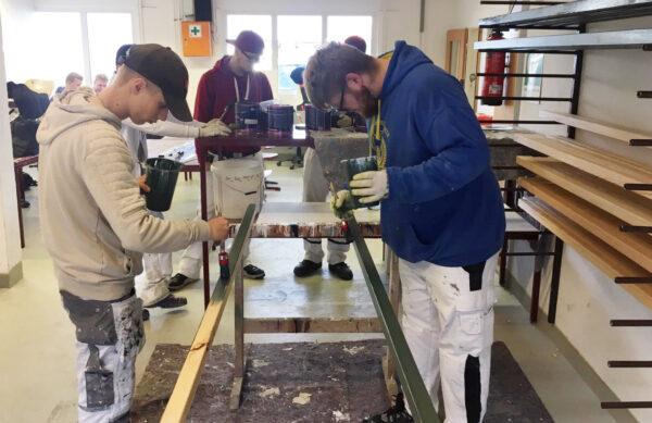 Die angehenden Bau- und Metallmaler setzen die Designs auf den Bänken passgenau um.